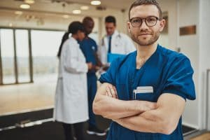 Confident relaxed surgeon doctor at hospital with team of doctors in background