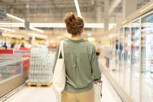 Young woman with shopping card and cotton shopper bag is shopping in supermarket. Copy space. Sustainable lifestyle. Sale, discount concept.